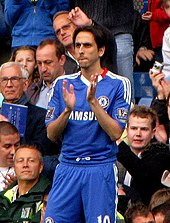 A photograph of a white man wearing blue association football attire while clapping his hands. Behind the player, several spectators can be seen looking at him.