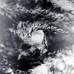 A visible satellite image of a very compact tropical storm, with a small and partially obscured eye in the center of its central dense overcast