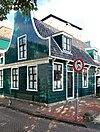 Houten huis met ingezwenkt voorschot, bekroond door een fronton