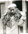 為1917年,一位男子脖子上掛著13,500個銅板。 銅錢貶值,物價上漲,購物時不得不背上幾十斤重的銅錢串。(Cropped).png