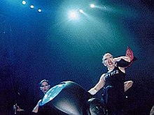 A blond woman sliding down from a car on stage, flanked by two female dancers. The woman wears a sleeveless coat and ties her hair in a knot, behind her.