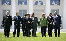une femme blonde en vert au milieu d'hommes en costume sombre