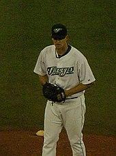 A Man In White Baseball Uniform Reading Jays Across The Chest Dark