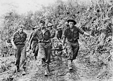 Soldiers carry a stretcher upon which another man lies