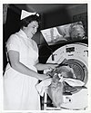 A nurse shares a smile with a child inside of an iron lung (13911641704).jpg
