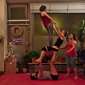 Acrobalance - Three people and a spotter performing a pyramid thighstand on throne