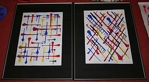 Two paintings (portrait orientation) are side by side with the only marks being thick lines that terminate with a sizeable dot of blue, yellow, or red. The left one has lines vertical/horizontal and he right one has lines diagonally.