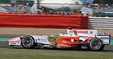 en vit och guld Formel 1-bil kör en kurs