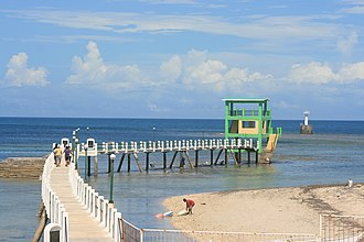 Madridejos, Cebu - Beach and walkway at Kota Point, with the light station visible past the end of the walkway.