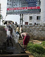 Billboard marketing gated community with workers bathing in Bangalore.jpg