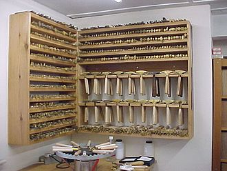 Bindery - Racks of brass tools and a finishing stove beneath.