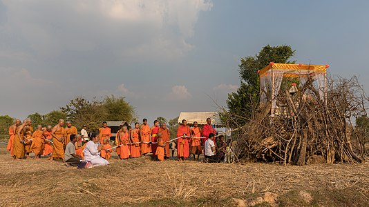 Buddhist monks procession in front of a pyre