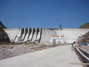 Bui Dam - Bui Dam, Ghana in November 2013 shortly before official opening. Looking upstream, approximately north-east. Powerhouse at right, with three orange penstocks visible above the roof (one for each generator). Spillway has five bays. The penstock for the future house unit is visible at the left. The dam crest is about 75 metres above the powerhouse main floor.  Powerhouse paved road under construction visible in foreground. Telpher construction crane  supported by cables has not yet been removed.