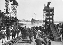 A large ship slides into the water. A tall crane stands on one side and a large scaffolding on the other. A crowd of spectators has gathered all around.