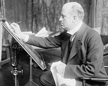 A man in late middle-age, facing left, drawing at an upright drawing board.
