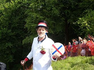 Cooper's Hill Cheese-Rolling and Wake - The Master of Ceremonies (MC) holding the cheese
