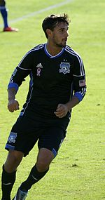 A man wearing a black jersey and black shorts, running on a soccer field.