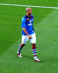 A man wearing a blue t-shirt and white shorts standing on a grass field
