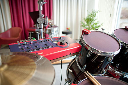 "Triggers sensors in use, here they are red and mounted on the rims of the snare drum, bass drum and hanging toms. The larger box in the same colour red is the ""brain"" to which they are connected. Clavia ddrum4 SE.jpg"
