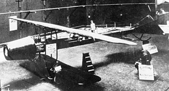 Coandă-1910 - An overhead view, showing the Clerget engine's four upright cylinders aft of the rotary compressor. Upper and lower wings are mounted on steel tubes extending from the fuselage. A man stands in the fuselage near two Antoinette VII-style trim and steering wheels.