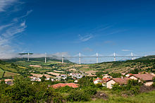 A view of the Millau Viaduct in the distance, the tops of some of its towers shrouded within the clouds. The village of Creissels is in the foreground.