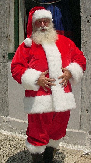 Santa suit - A red Santa suit, with white fur trim, stocking cap, and black boots; a wide buckled belt typically included is not present here