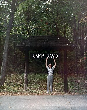 David Eisenhower - Eisenhower (age 12) poses with sign at presidential retreat named in his honor, 1960.