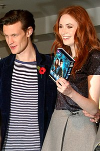 Matt Smith and Karen Gillan are turned to the side and smiling as if taking a picture. Gillan is holding up a DVD boxset of the series.