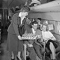 Een stewardess deelt flesjes drank uit, Bestanddeelnr 252-2070.jpg