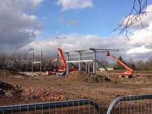 A muddy construction site with two vehicles working to build the stadium during the day. A small steel structure has been created which is beginning to resemble a football stand. The sky is lightly cloudy and in the background there are trees.