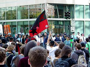 October Rebellion - A demonstrator waves a red and black flag during an intersection occupation outside the World Bank.