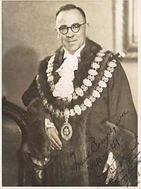 Middle aged man with receding dark hair, wearing circular glasses. He is wearing a dark robe with two chains of circular decorative disks, a fluffy light-coloured tie, and is standing next to a ceremonial chair. The subject of the photograph has signed it.