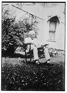 Black and white photograph of an elderly man sitting on a chair in a garden