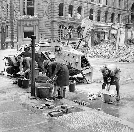 German women washing clothes at a water hydrant in a Berlin street. A knocked-out German scout car stands beside them, 3 July 1945. German women doing their washing.jpg