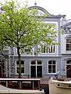 foto van Pand met gepleisterde lijstgevel met stucversieringen. Segmentvormig fronton