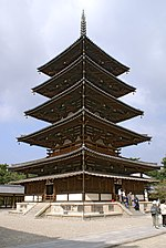 Wooden five-storied pagoda with white walls. Below the first roof, there is an additional attached pent roof.