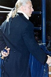 Helmsley indossa un frac e qui ha una tradizionale bottiglia spray per evidenziare il suo snobismo effeminato.