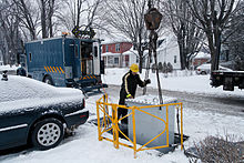 A man with a hard hat helps a machinery operator lower a transformer to an underground pit in a residential neighborhood. The roads and cars are covered with snow.