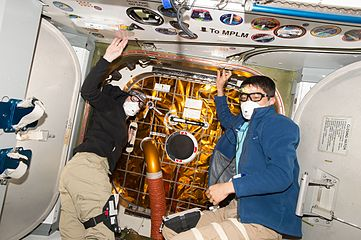 ISS-48 Kate Rubins and Takuya Onishi open the SpaceX CRS-9 hatch.jpg