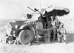 Officers of the 11th Hussars using a parasol to give shade during a halt, while out patrolling on the Libyan frontier, 26 July 1940. The vehicle is a Morris CS9 armoured car. IWM-E-380-Morris-CS9-libyan-frontier-19400626.jpg
