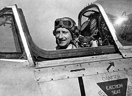 Man in flying cap and goggles sitting in aircraft cockpit