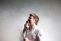 Viro kantas al mikrofono tenante tamburbastonojn.
