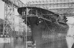 A large ship, covered with scaffolding, sits in harbor under a large gantry.