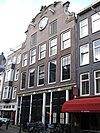 foto van Koetshuizengroep met bovenwoningen, achter gemeenschappelijke gevel onder brede klokvormige top met a-jour vierpas