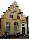 foto van Huis met gepleisterde trapgevel met zandstenen waterlijsten en afdekplaten en halfronde top met pilasters en voluten