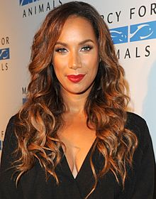 A woman with long, curly brown hair looking directly forward, wearing a black outfit, and red lipstick.