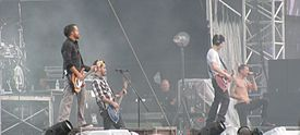 A color photograph of members of the group Linkin Park performing on and outdoor stage