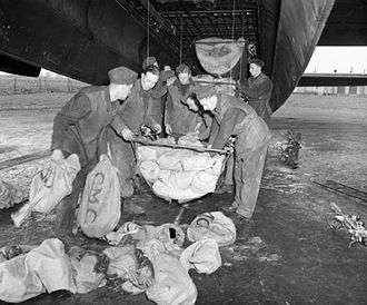 Operations Manna and Chowhound - RAF ground crew loading food supplies into slings for hoisting into the bomb bay of an Avro Lancaster heavy bomber of 514 Squadron (1945).