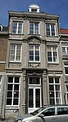 Huis met sierlijke lijstgevel van Naamse steen in Lodewijk XVI-stijl.