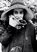 Photo of a woman holding an ear trumpet to her ear.